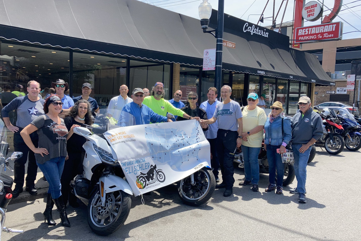A group of folks outside posing next to a motorbike on a sunny day.