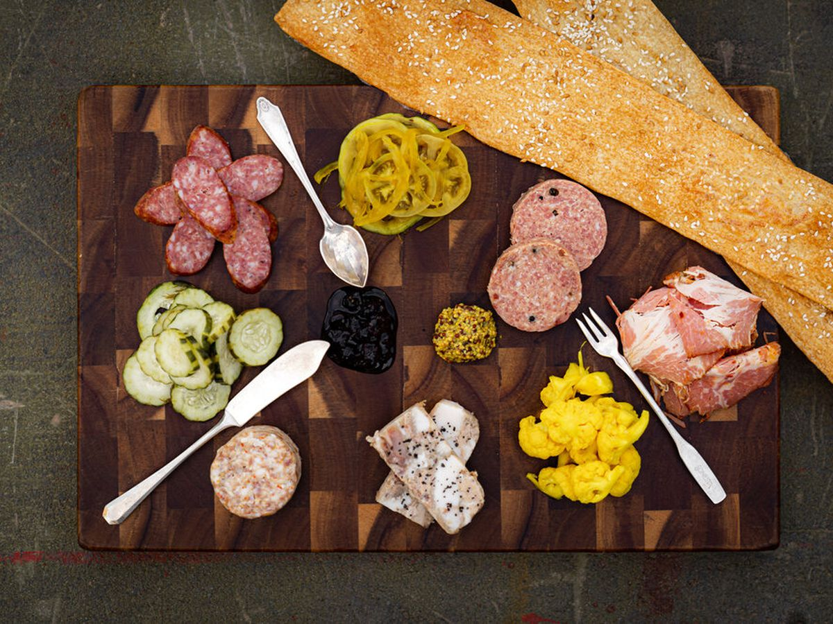 Charcuterie platter with garnishes and metal spoons from Persepshen