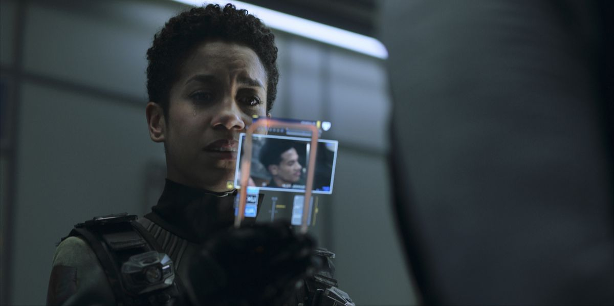 Naomi Nagata, played by Dominque Tipper, looks at a high-tech handheld photo display with apparent distress in The Expanse