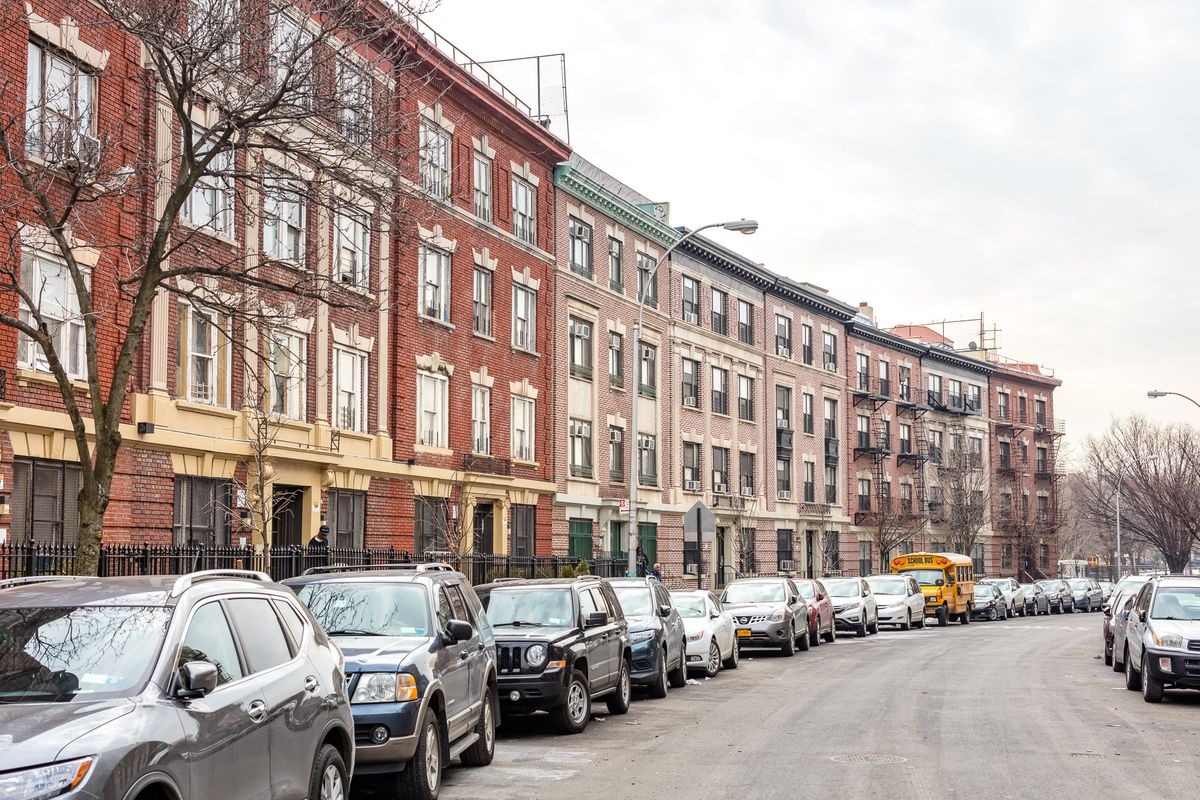 A row of eight red and light brick apartment buildings on a car-lined street in the Longwood section of the Bronx.