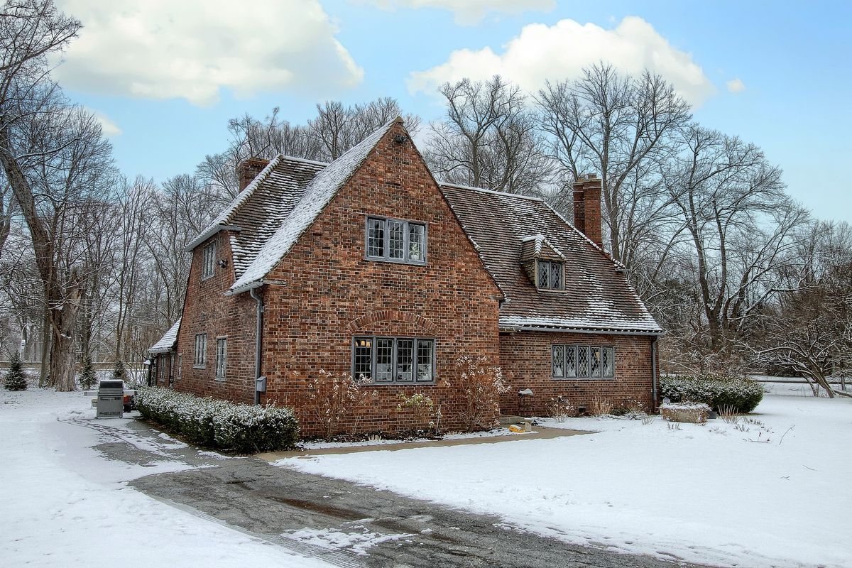 A two-story brick home with varied roofline and leaded-glass windows. There's snow covering the roof and lawn.