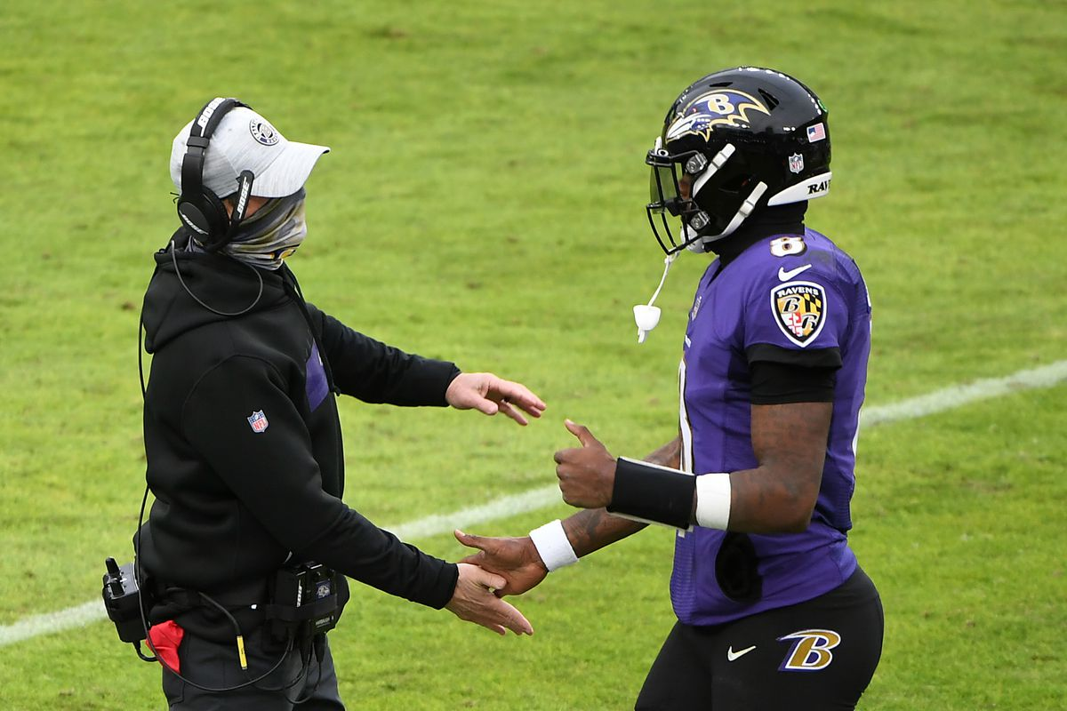 Quarterback Lamar Jackson #8 of the Baltimore Ravens celebrates with head coach John Harbaugh following a touchdown drive during the third quarter of their game at M&T Bank Stadium on December 20, 2020 in Baltimore, Maryland.