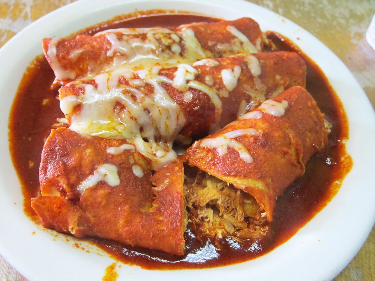 Three enchiladas painted with a deep red sauce and melted squiggles of cheese.