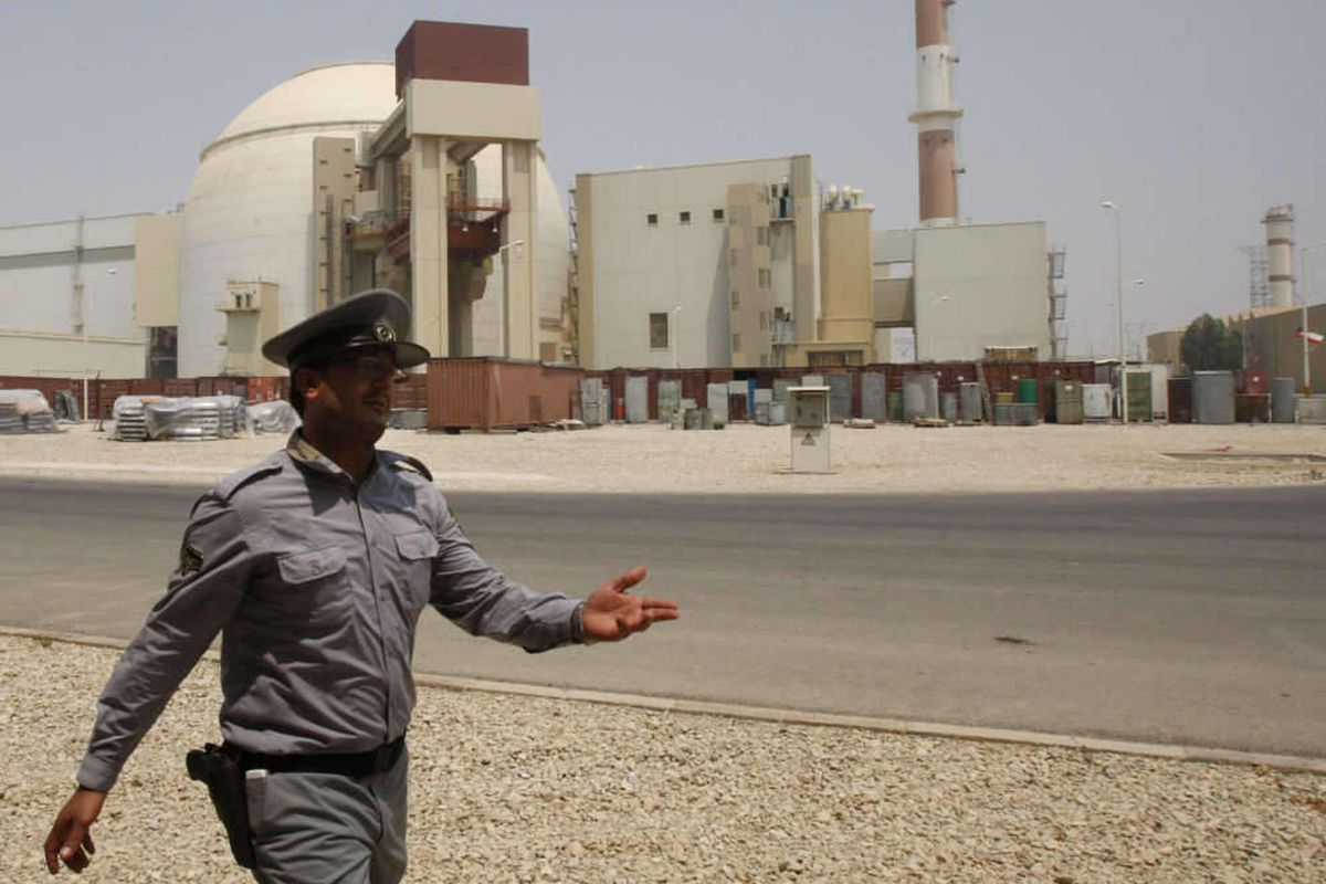An Iranian security directs media at the Bushehr nuclear power plant, with the reactor building seen in the background, just outside the southern city of Bushehr, Iran, Saturday, Aug. 21, 2010.