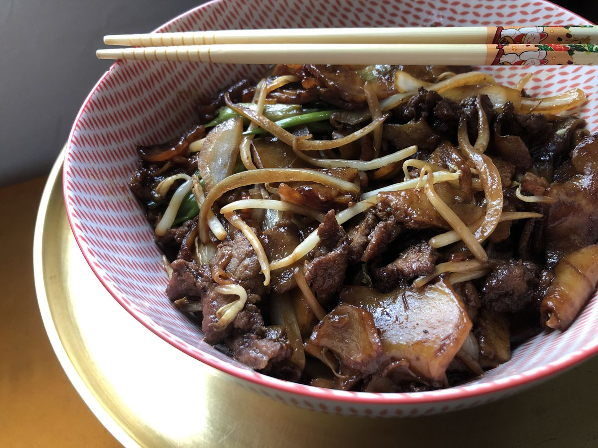 A bowl of chow fun with slices of beef and vegetables, in a decorative bowl on a charger