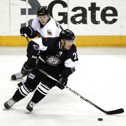 Judd Blackwater of Las Vegas controls the puck with Gaelan Patterson of Utah in the background as the Utah Grizzlies face the Las Vegas Wranglers in ECHL hockey at the Maverik Center in West Valley City, Monday, April 2, 2012.