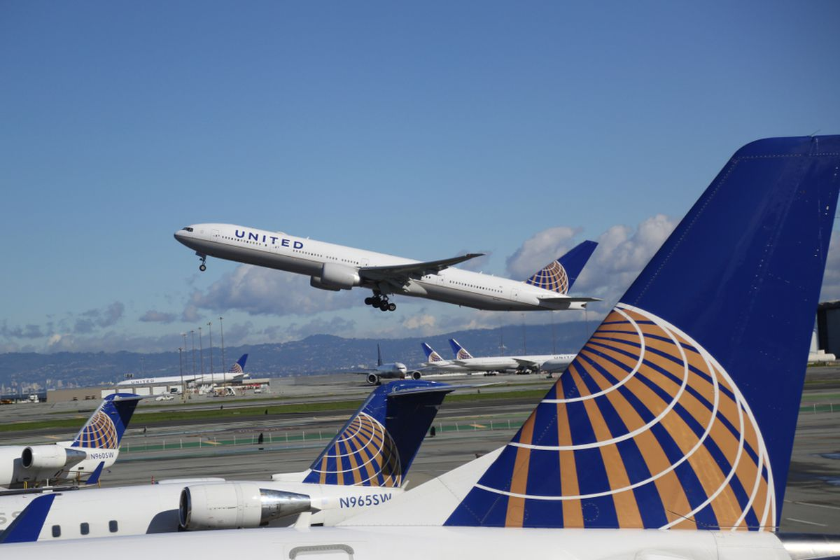 An airliner taking off, with the large tail of a different plane in the foreground.