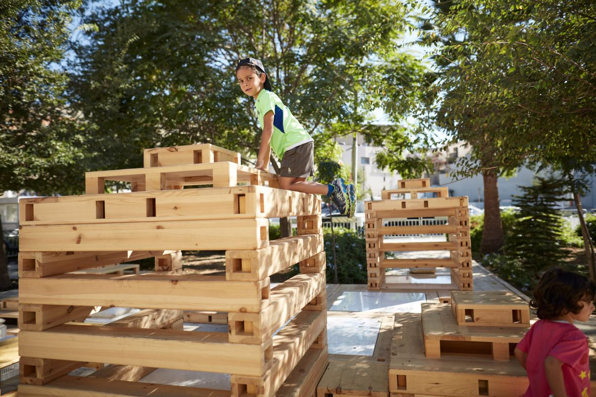A series of stacked wooden pallets in tree-surrounded square with a child climbing on one.