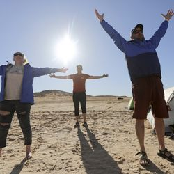 Ashton Hintze, a 17-year-old who is legally blind due to Stargardt disease, left, Ryan Greene, Utah Schools for the Deaf and the Blind principal and director of blind campus programs, and Brandon Watts, the school's director of outreach visions services, do yoga after a long day of paddling on Lone Rock Beach at Lake Powell on Saturday, March 27, 2021. They are part of the school's yacht club, which is training for the SEVENTY48, a 70-mile human-powered boat race from Tacoma to Port Townsend, Wash. Members of the yacht club built their boat for the race by hand.