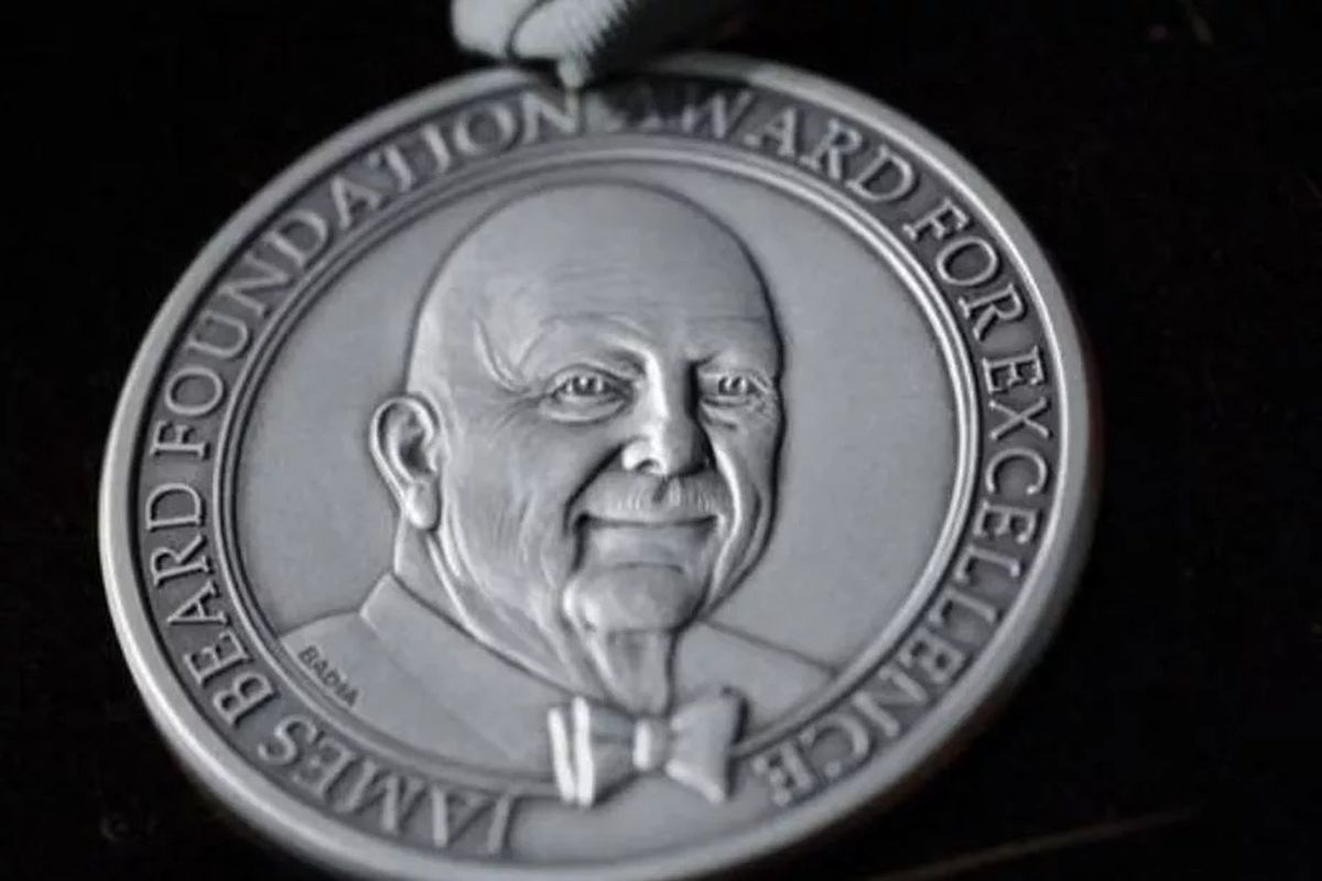 A silver medallion with a portrait of famous cookbook author James Beard wearing a bow tie