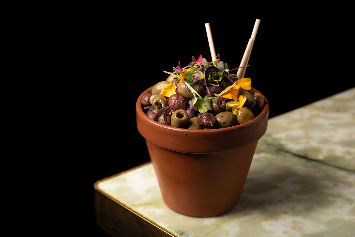 Marinated olives served in a clay planter on a marble table.
