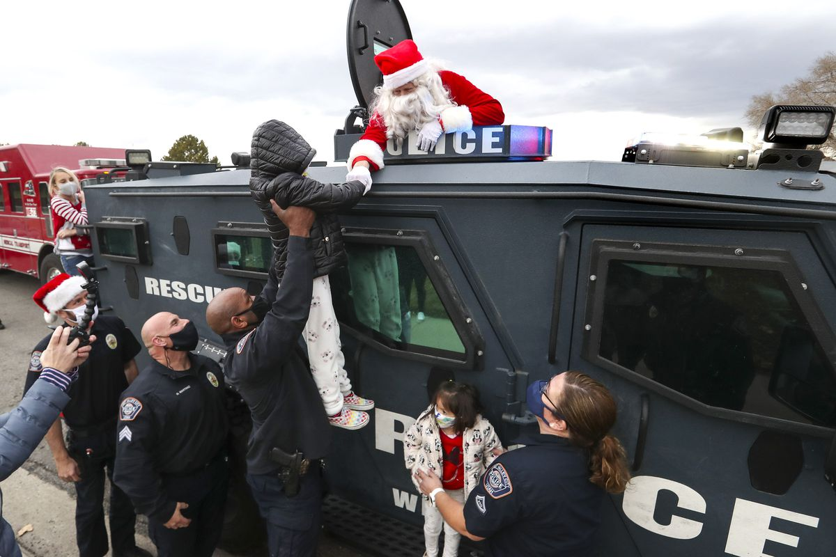 Santa fist-bumps children from an armored West Valley police vehicle during the department's Giving Tree event in West Valley City on Tuesday, Dec. 22, 2020. The program provided gifts for 159 children from 51 low-income families in the city that were delivered to their homes by police officers. Each child started with a list of needed items and holiday wishes. Santa's helpers from the police department, local businesses and the community then worked hard to fulfill the wishes.