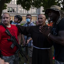Kevin Mathewson, left, a former Alderman of Kenosha, speaks with a Black Lives Matter activist, right, while Brother Chuck, a Franciscan Fryer, moderates the discussion, during a protest over the shooting of Jacob Blake, Tuesday, Aug. 25, 2020, in Kenosha, Wis.