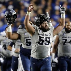 Utah State players celebrate at halftime with a lead over BYU during NCAA football in Provo, Friday, Oct. 3, 2014.