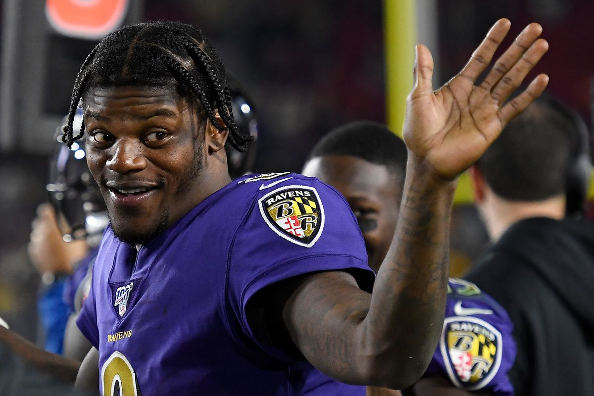 Quarterback Lamar Jackson of the Baltimore Ravens waves from the sidelines during the game against the Los Angeles Rams at Los Angeles Memorial Coliseum on November 25, 2019 in Los Angeles, California.