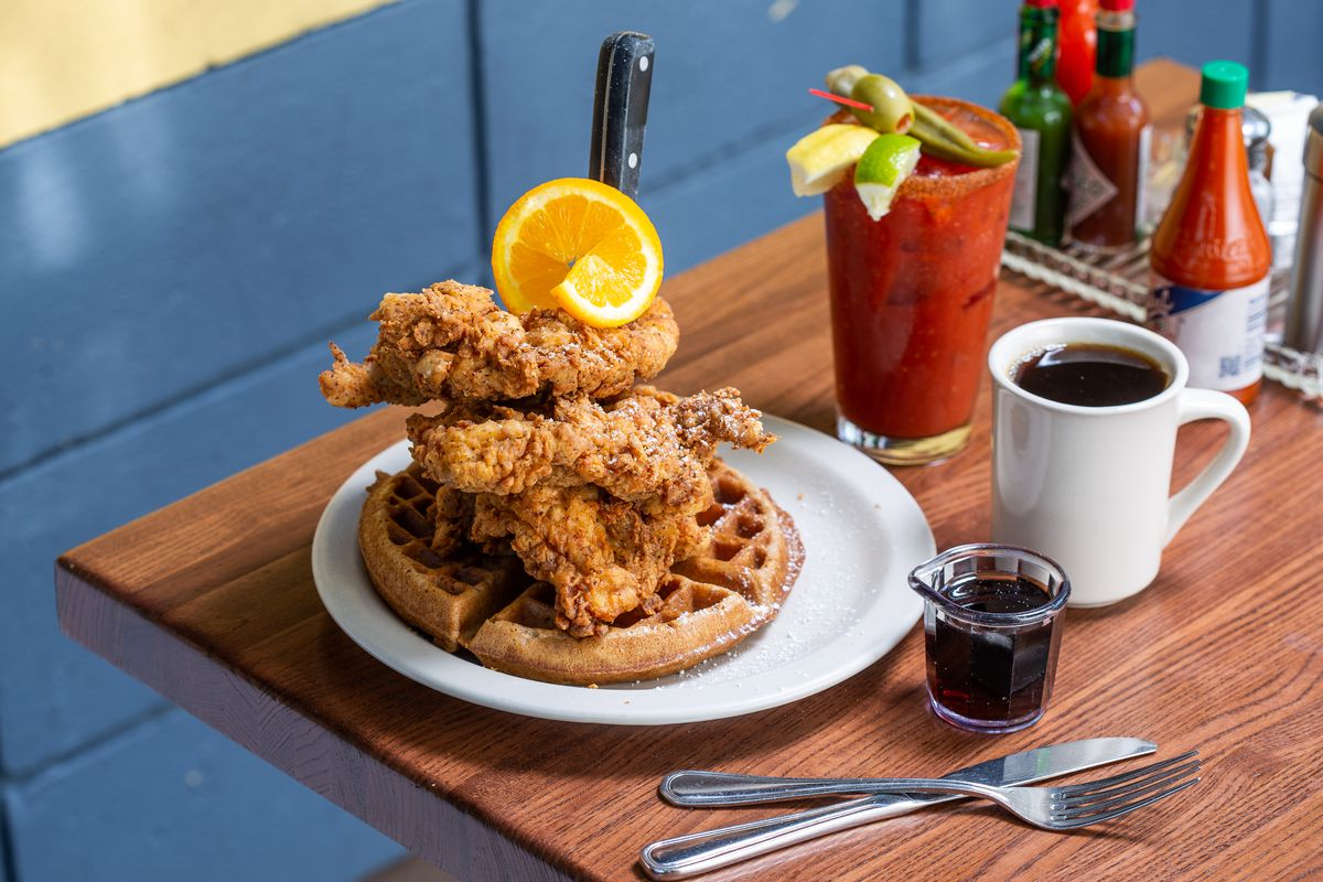 A tower of fried boneless chicken sits on top of a waffle with an orange slice, held in place with a knife, at Screen Door. Next to the plate sits a cup of coffee and a bloody mary, with a side of syrup and Crystal hot sauce.