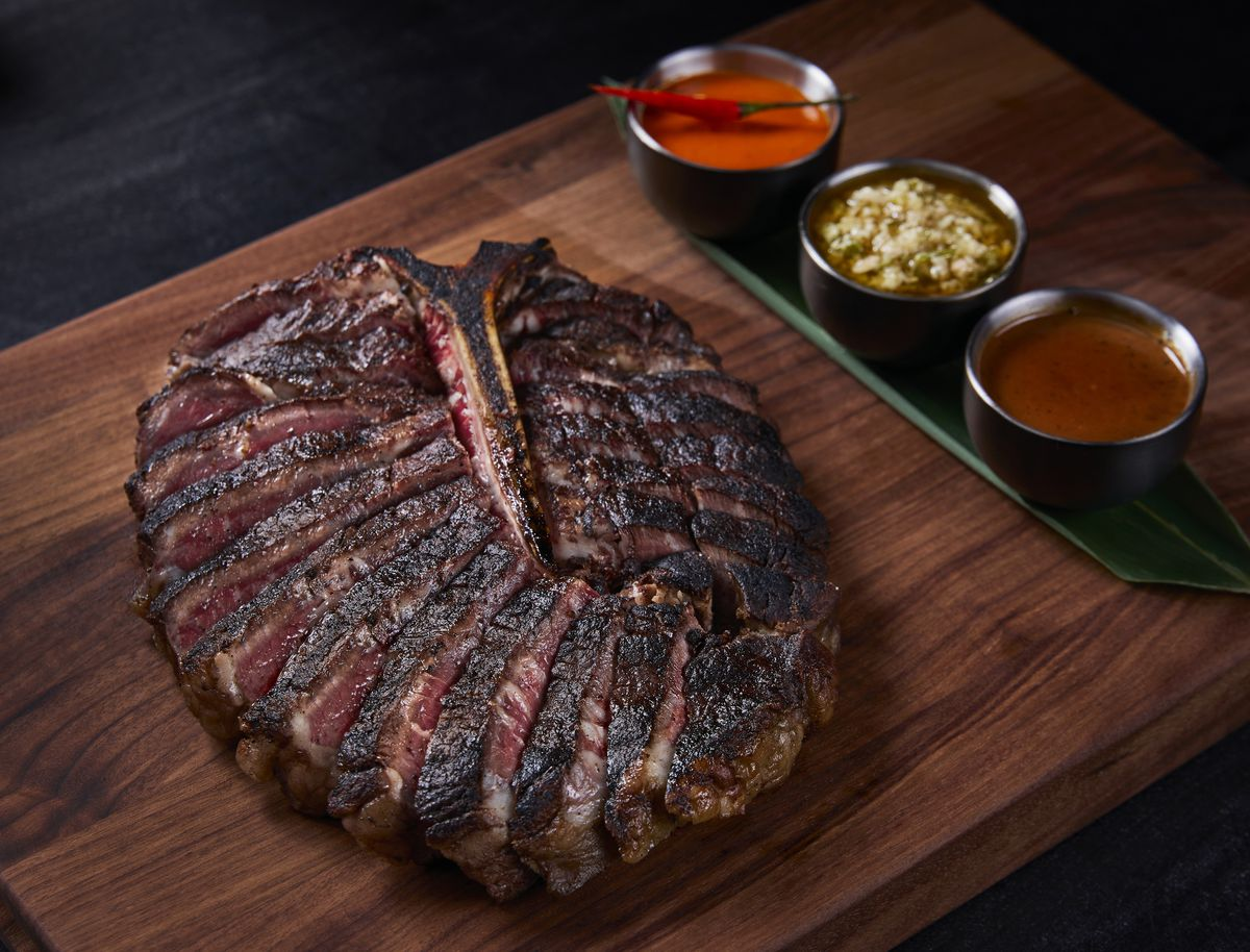 steak sliced on a wooden board with sauces on the side