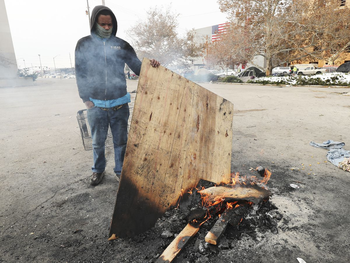 Tyrell Morris, who is homeless, tends a fire for warmth on 700 South in Salt Lake City on Tuesday, Nov. 10, 2020. The Kem C. Gardner Policy Institute on Tuesday published a report identifying major problems within the state's current homeless governance structure.
