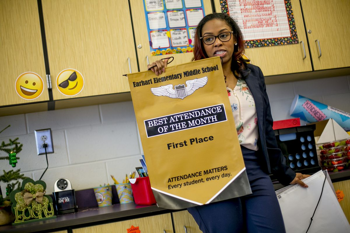 Attendance agent Amanda Bowman presents a banner to the class at Earhart Elementary-Middle School that had the best attendence in February. Students in that class were allowed to come to school out of uniform the following week.