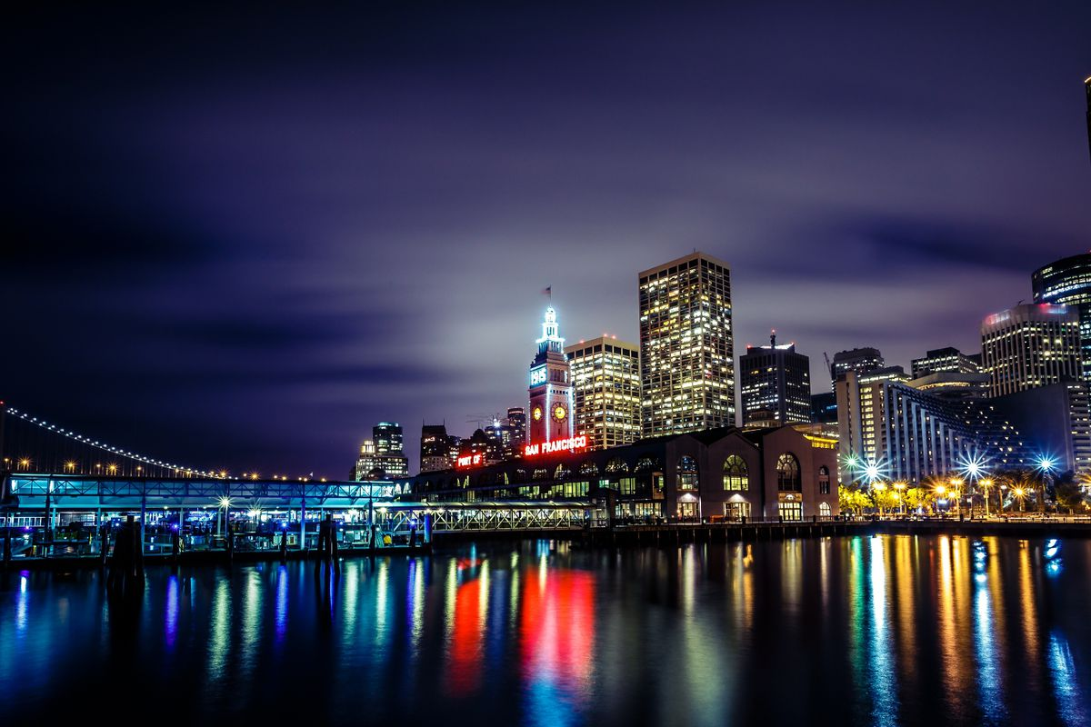 The San Francisco skyline at night, as seen from the bay on an overcast day with city lights reflecting off the clouds.