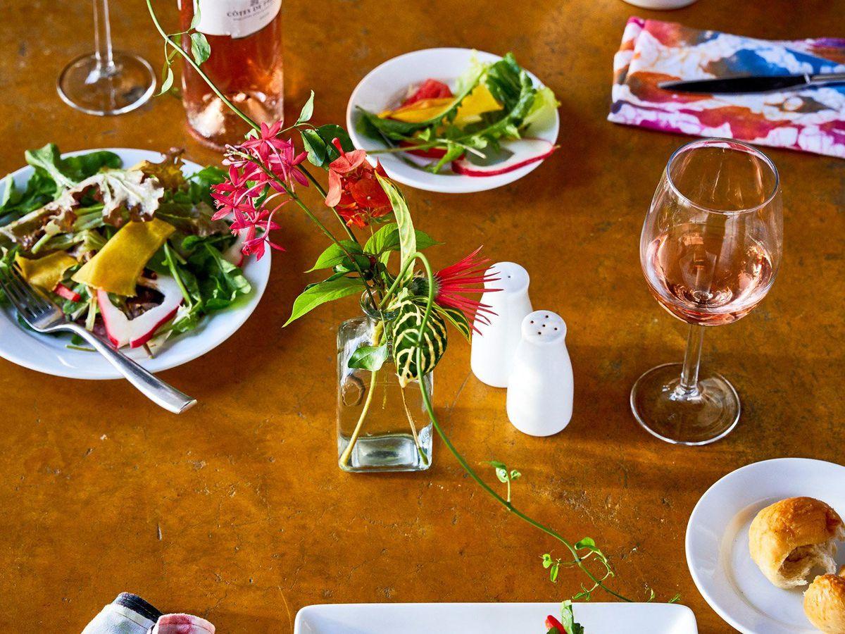 一张木桌,上面放着鲜花、盐和胡椒,还有许多盘沙拉。