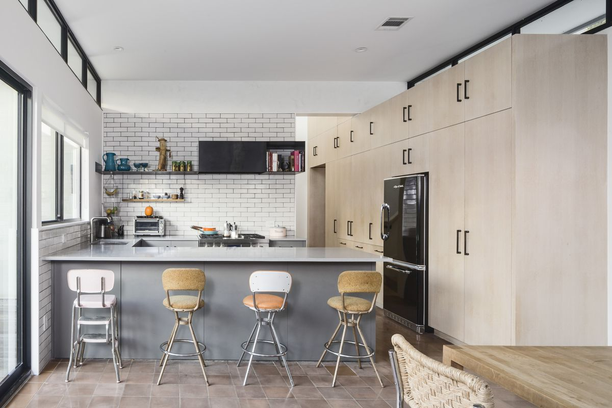 Contemporary/modern kitchen with bar and light wood cabinets, subway tile, clerestory and regular windows