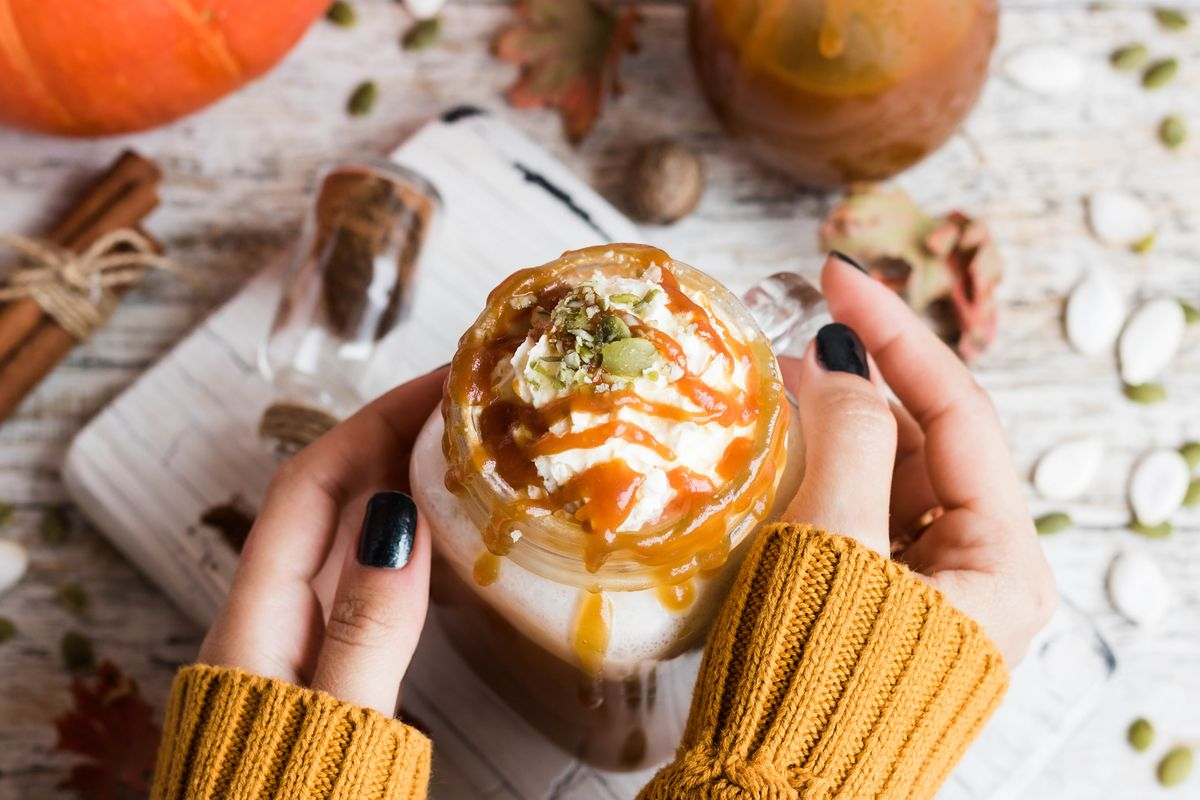 A woman's hands with dark blue nail polish hold a decadent pumpkin spice latte. She's wearing a yellow sweater and is surrounded by pumpkins, seeds, and spice mix.