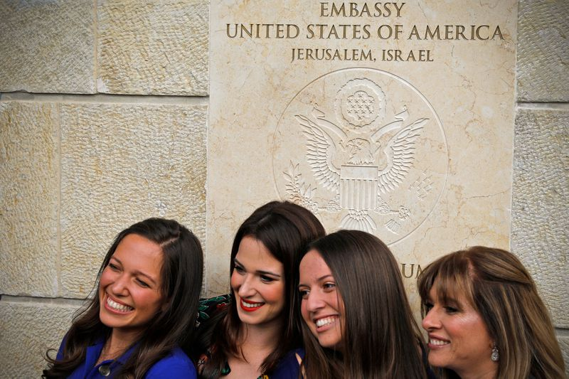 Women pose for a picture next to an inauguration plaque.
