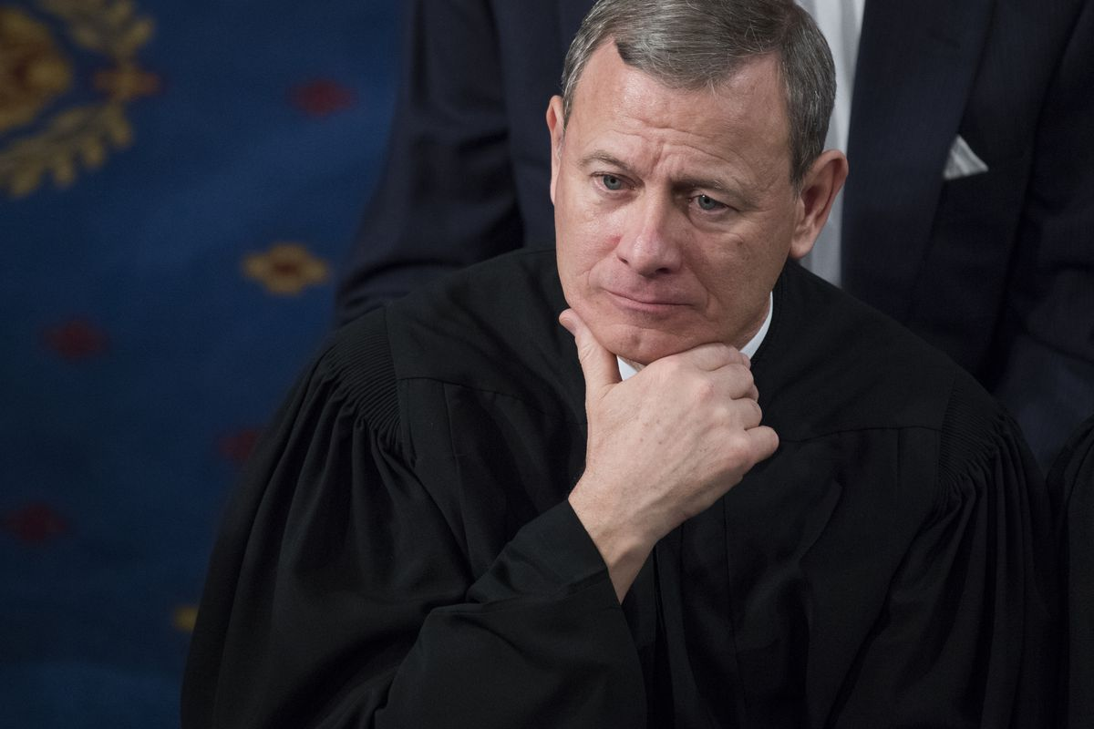 Supreme Court Chief Justice John Roberts holding his chin in his hand.
