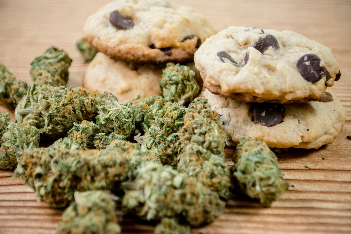 A pile of marijuana buds in front of choc-chip cookies.