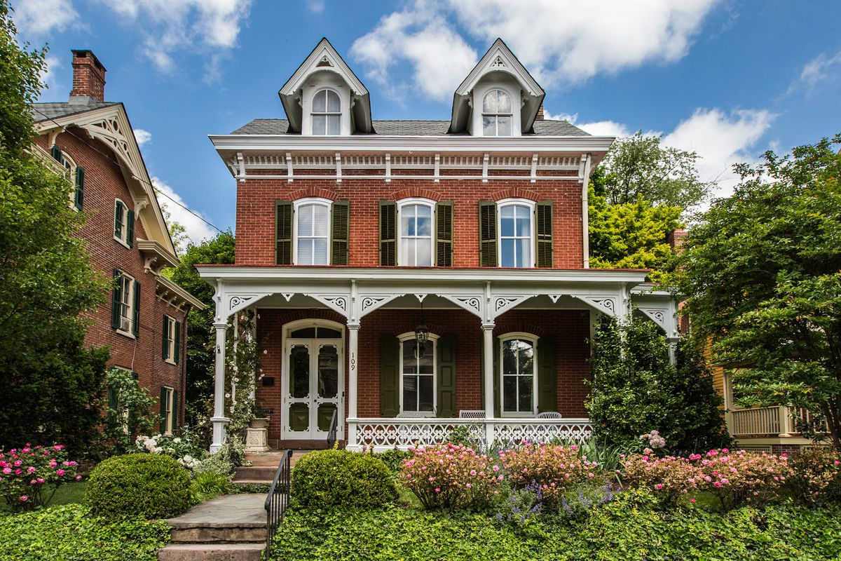 Brick Victorian home with front porch with wood trim and shuttered windows.