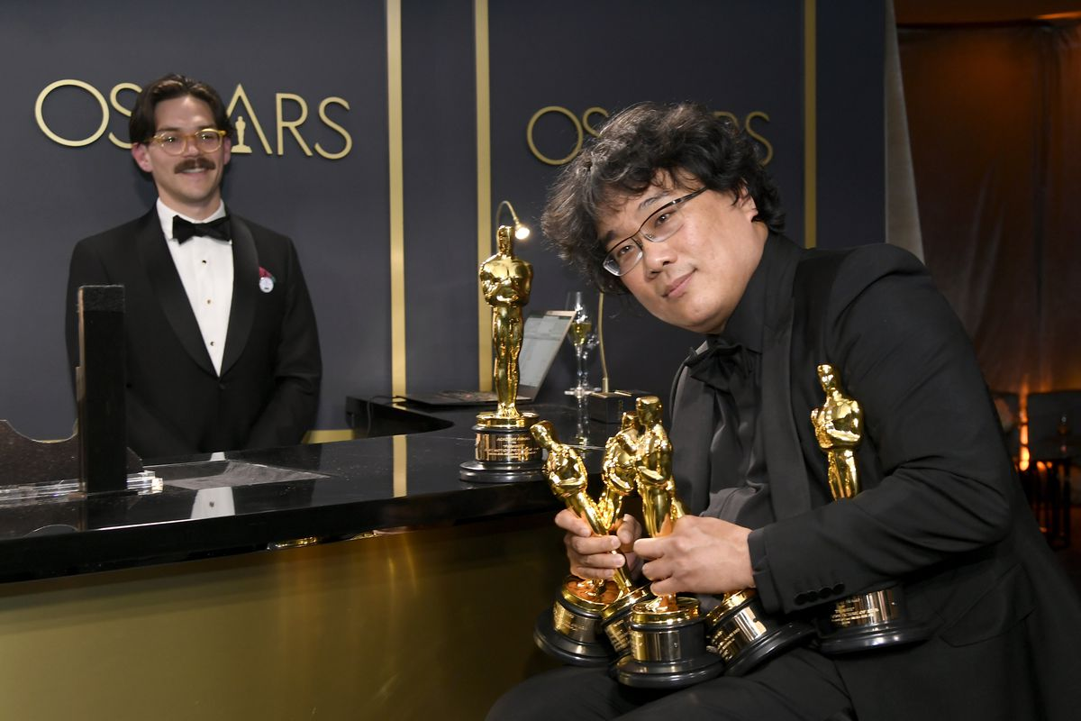 Director Bong Joon-ho clutches five Oscars to his body while sitting behind the scenes at the 92nd Academy Awards ceremony.