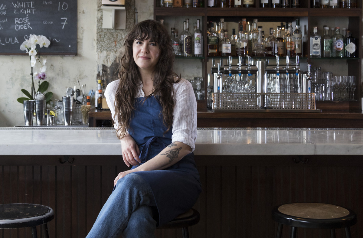 A woman with long hair sitting in front of a bar in jeans, a white blouse and a blue apron.