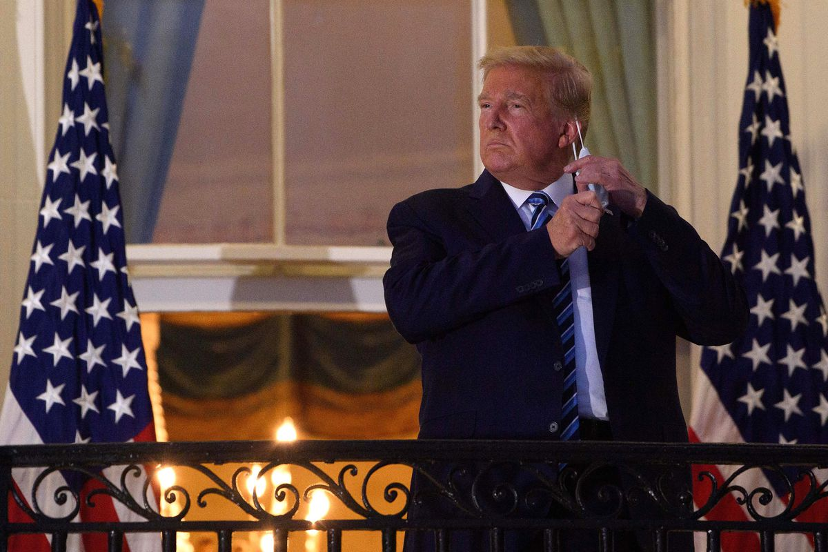 President Trump outside on a White House Balcony taking off a face mask.