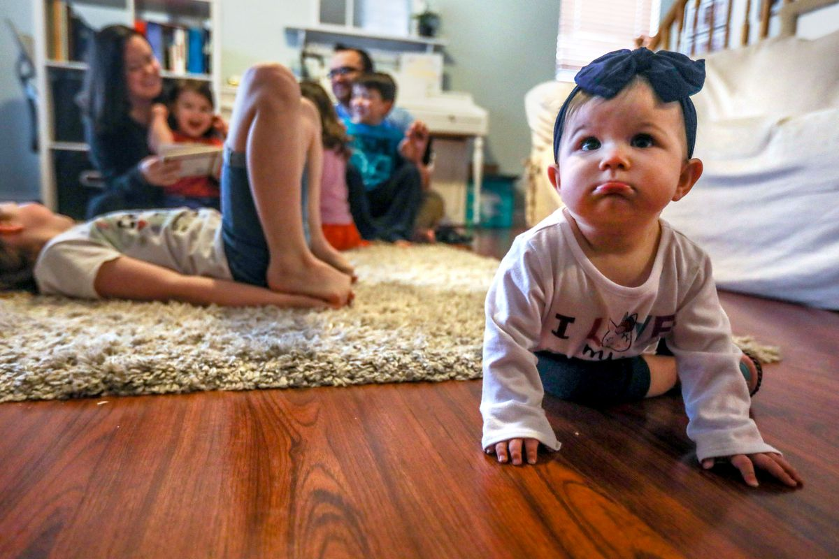 Minerva Reed crawls around while her family play and relax in their home in Eagle Mountain on Saturday, March 20, 2021. At 35 weeks pregnant soon after the pandemic started, Dani Reed switched her birth plan to have a home birth so her family could be there.