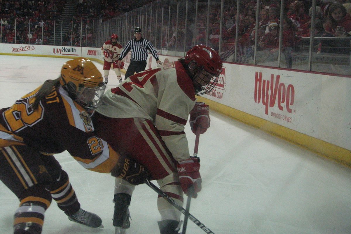 Wisconsin's Madison Packer and Minnesota's Hannah Brandt dig for the puck along the boards.