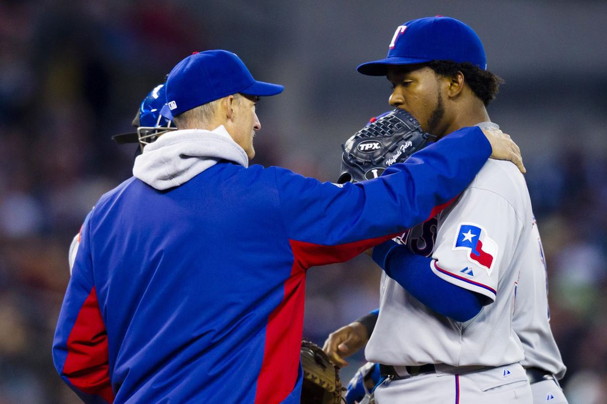 April 21, 2012; Detroit, MI, USA; Texas Rangers pitching coach Mike Maddux (left) talks to starting pitcher Neftali Feliz (right) during the fourth inning against the Detroit Tigers at Comerica Park. Mandatory Credit: Rick Osentoski-US PRESSWIRE
