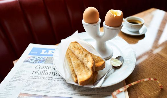 Eggs and soldiers with a newspaper at Colbert restaurant