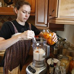 Aimie Buxton saves money on food buy making her own yogurt-like kefir daily from kefir grains and milk and adding fruit to make smoothies for her family. Here she is adding canned apricots from her mother's tree.