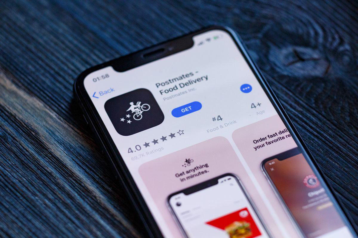 A cell phone displays the Postmates logo in an app store.