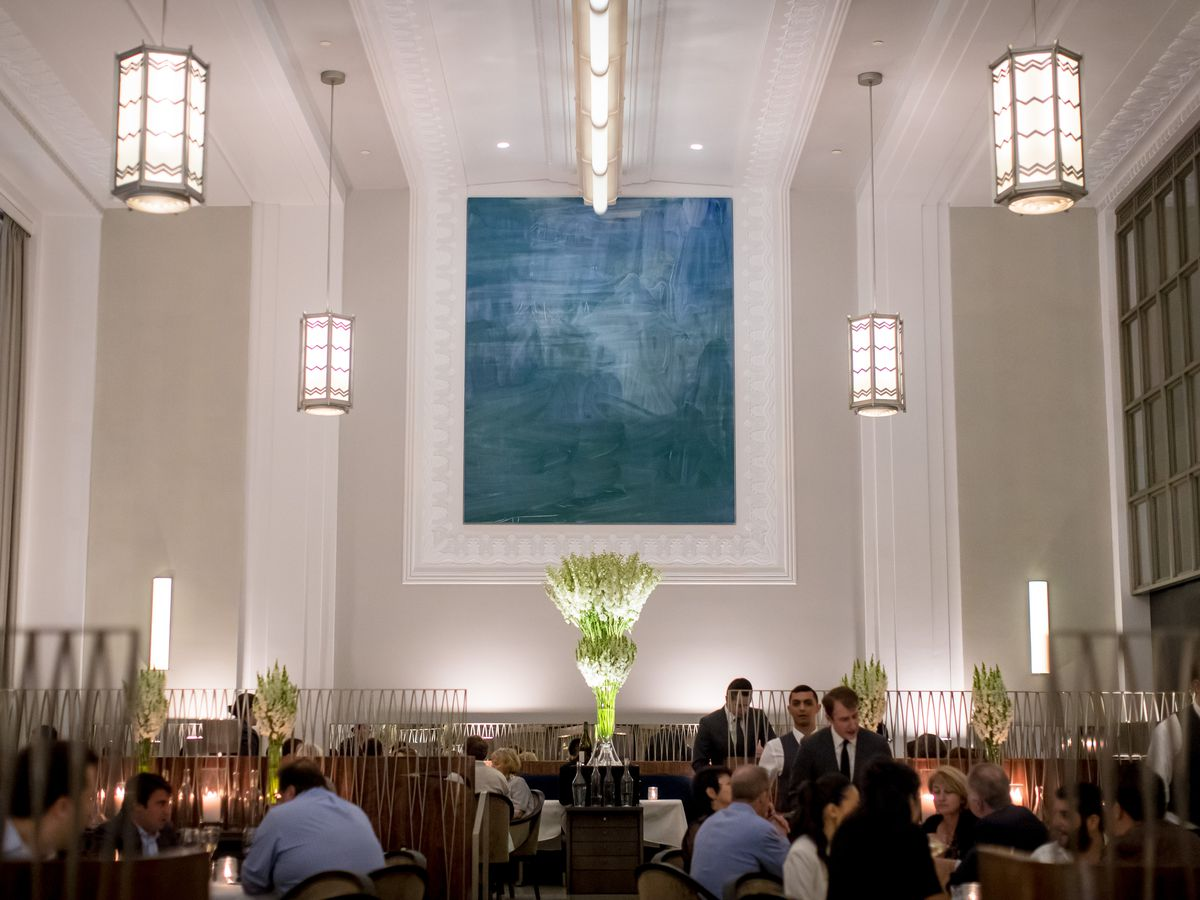 The grand dining room at Eleven Madison Park with a large blue painting and high ceilings