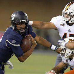 Utah State quarterback Jordan Love (10) carries the ball as Idaho State linebacker Oshea Trujillo (45) and defensive back Adkin Aguirre defend during an NCAA college football game Thursday, Sept. 7, 2017, in Logan, Utah. (Eli Lucero/Herald Journal via AP)