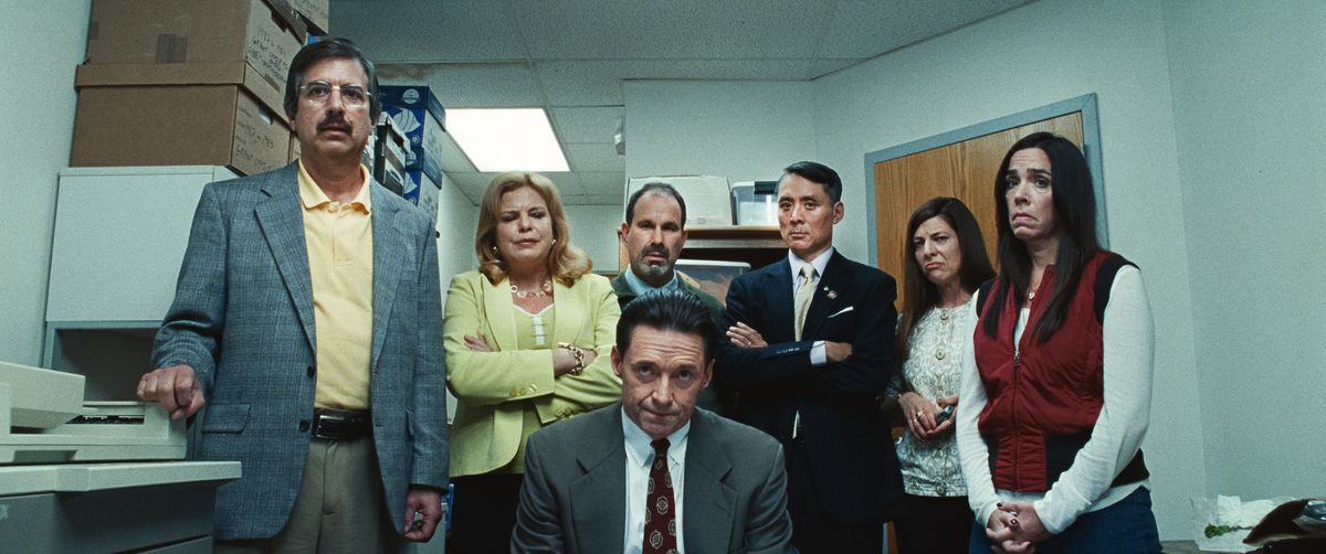 Hugh Jackman, dressed in a gray suit and red tie and looked disheveled on camera, confronting a hidden man. Behind him, six school board members stand in a circular, similarly unhappy or angry look, looking at this subtle person.