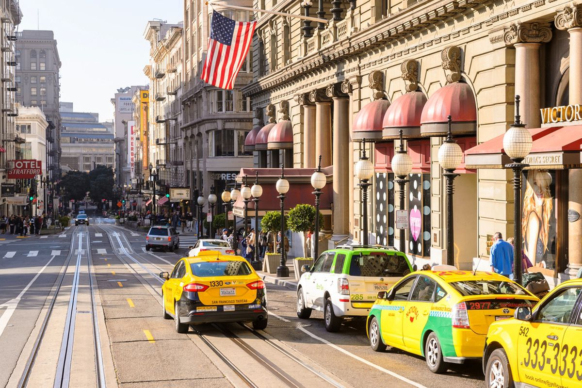 Taxi cabs driving by Union Square in SF.