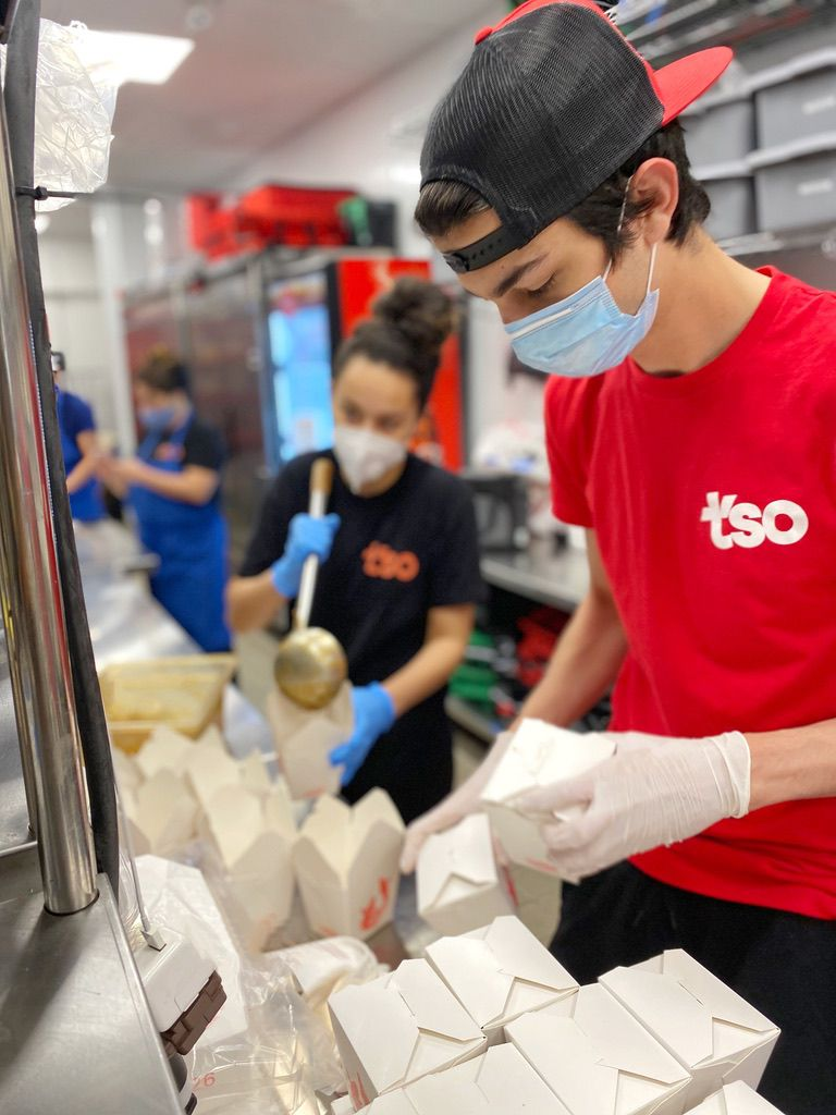 A white boy in a blue surgical mask, a backwards baseball cap, and a red Tso shirt packs Chinese takeout containers.