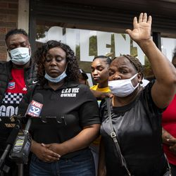 Renee Moore, mother of Verndell Smith, with her hand raised in the air speaks to reporters at Ultimate Threat Dance Organization's studio, Thursday, May 20, 2021. Verndell Smith, the founder of the dance studio was shot and killed yesterday.