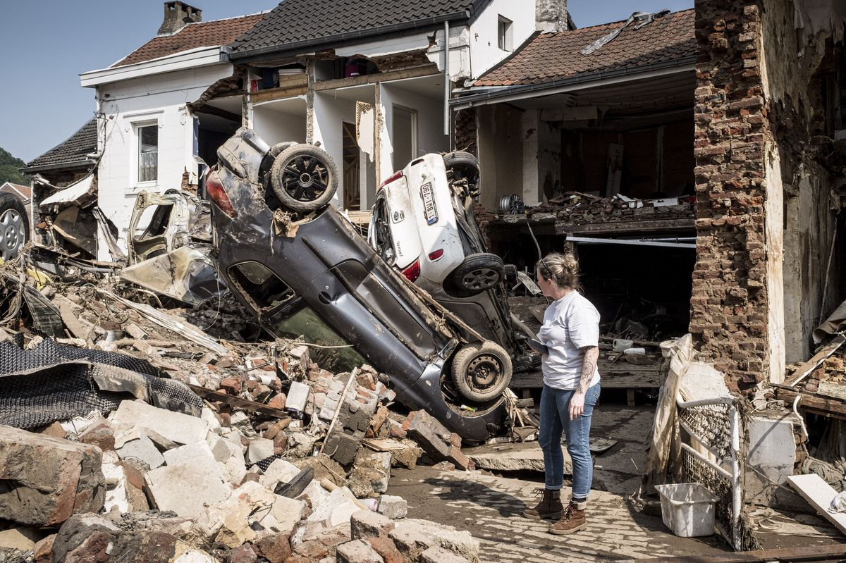 In this file photo dated Monday, July 19, 2021, a woman looks at cars and homes damaged after torrential rain caused flooding in Liege, Belgium.