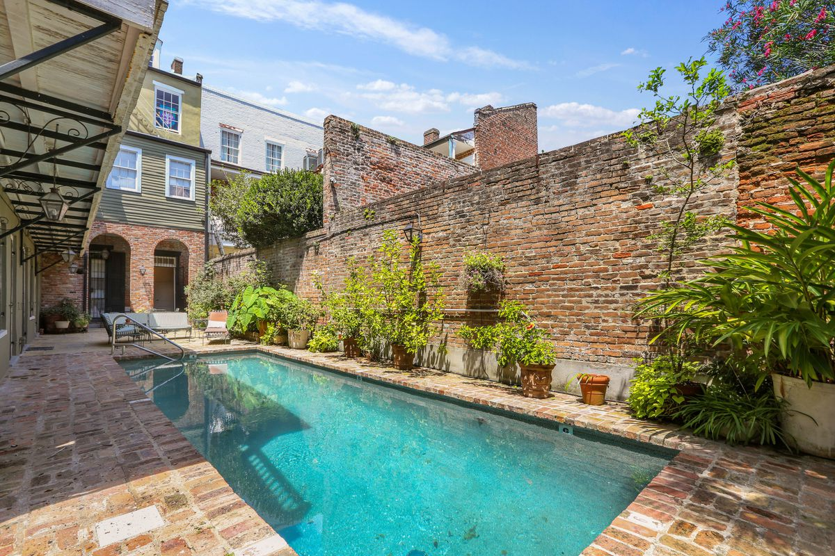 A pool in a brick courtyard with a blue sky and high brick walls.