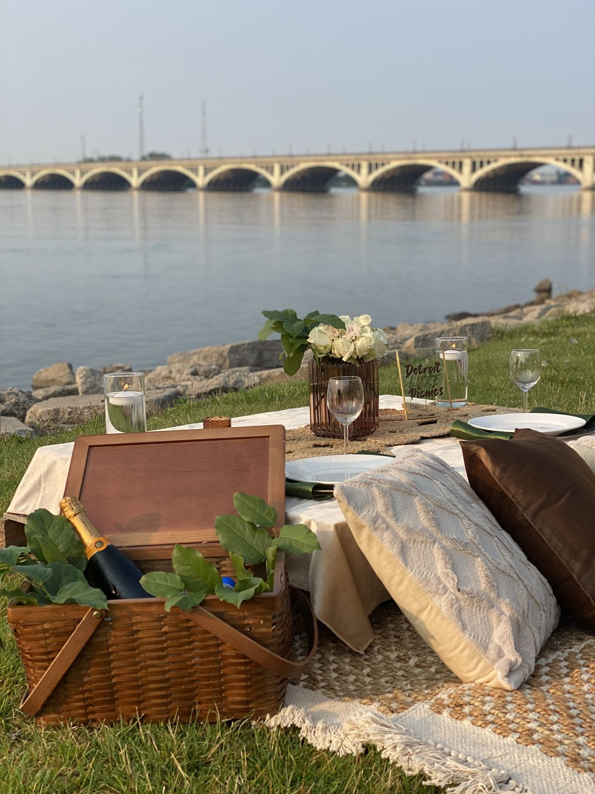 A picnic basket holding bubbly is propped against a table. Large pillows rest against the table. The MacArthur Bridge is shown over the Detroit River.