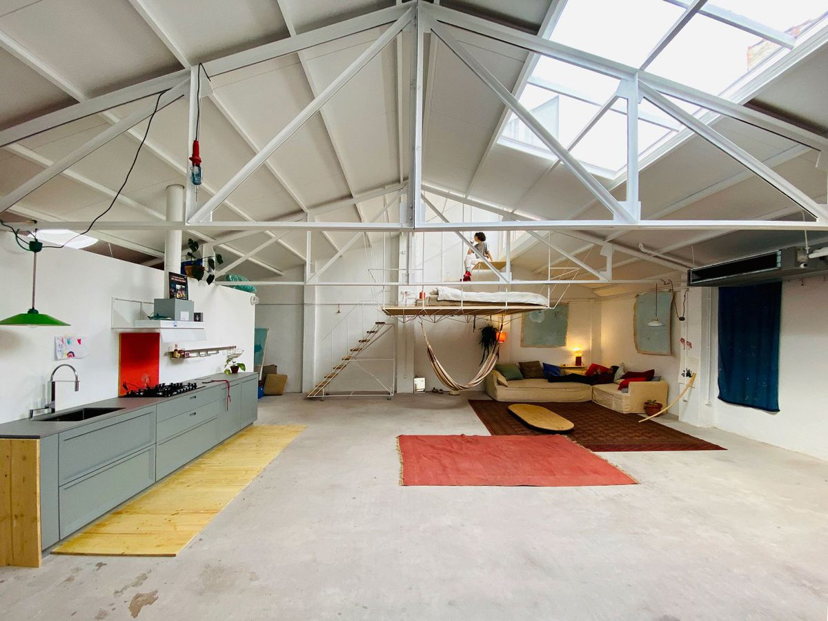 An airy warehouse space with exposed beams and skylights.